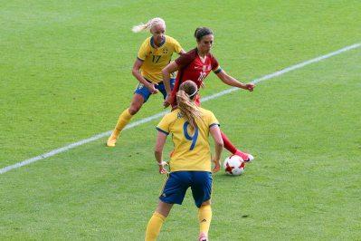 Carli Lloyd med Caroline Seger i ryggen
